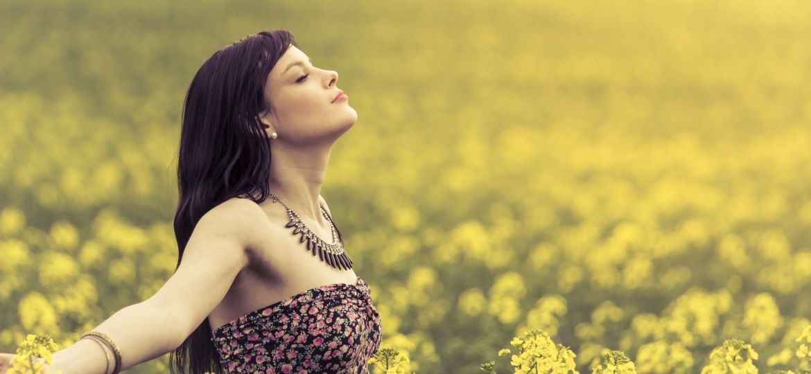 Happy positive woman in sunny summer ocean of yellow flowers
